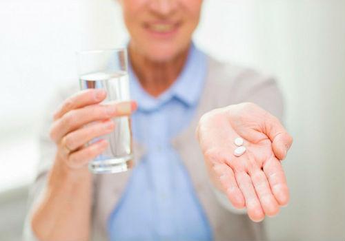 лекарство и стакан воды в руках