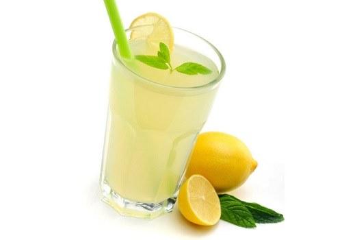 Стакан с лимонным соком и лимоны